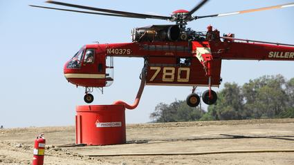 A Sikorsky S-64 Skycrane drafts Phos-Chek at heliport above Monrovia County Park for drops on the Station Fire